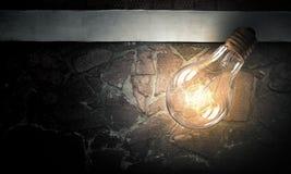 Электрическая лампочка на поверхности кирпича Стоковые Изображения