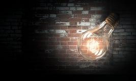 Электрическая лампочка на поверхности кирпича Стоковое Фото