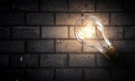 Электрическая лампочка на поверхности кирпича Стоковые Фото