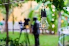 Электрическая лампочка на проводе строки с запачканной предпосылкой Стоковая Фотография RF