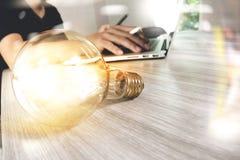 Электрическая лампочка при дизайнерская рука работая с портативным компьютером и c Стоковые Фотографии RF