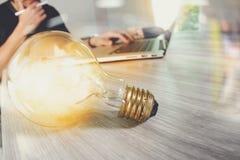 Электрическая лампочка при дизайнерская рука работая с портативным компьютером и c Стоковые Изображения RF