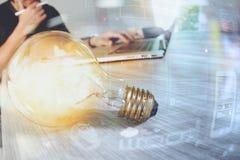 Электрическая лампочка при дизайнерская рука работая с портативным компьютером и c Стоковое Изображение RF