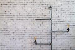 Электрическая лампочка с трубой металла над предпосылкой кирпича стоковые фото