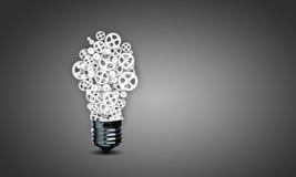Электрическая лампочка с шестернями Стоковая Фотография