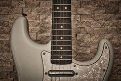 Электрическая гитара против стены текстурированной камнем Стоковое Изображение