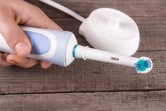 Электрическая зубная щетка в руке на старой деревянной предпосылке Стоковое фото RF