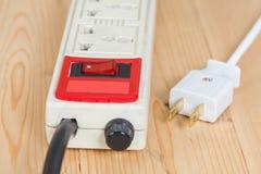 Электрическая штепсельная вилка на деревянном Стоковая Фотография