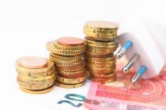 Электрическая штепсельная вилка с деньгами и монетками Стоковое Фото