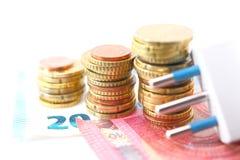 Электрическая штепсельная вилка с деньгами и монетками Стоковые Изображения