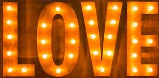 Электрические лампочки влюбленности знака на деревянной предпосылке Стоковое Изображение RF