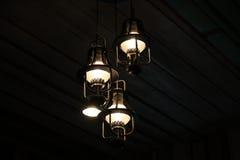 Электрические лампочки на черной деревянной предпосылке Стоковые Фотографии RF