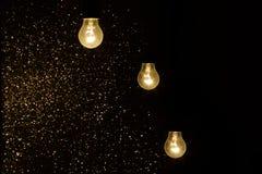Электрические лампочки на черной предпосылке с sparkles Стоковые Фотографии RF