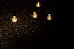 Электрические лампочки на черной предпосылке с sparkles Стоковое фото RF