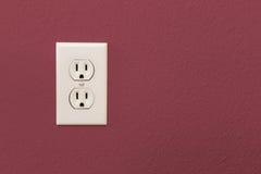 Электрические гнезда в красочной бургундской стене Стоковые Изображения