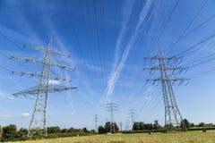 Электрические опоры транспортируя электричество до высокая напряженность ca стоковая фотография rf