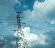 Электрические поляки высокого напряжения в белом облаке и голубом небе/электрических линиях электропередач и проводах поляка с го Стоковое фото RF