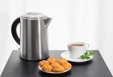Электрические чайник, чашка чаю и печенья на таблице Стоковые Изображения