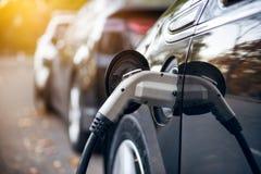 Электрический автомобиль поручая на месте для стоянки с зарядной станцией электрического автомобиля на улице города стоковое фото