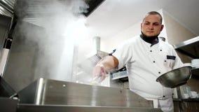 Электрический гриль на профессиональной кухне ресторана, кашевар очищает кухонные приборы, wipe с влажным паром ткани