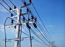Электрический поляк соединяется к высоковольтным электрическим проводам на предпосылке голубого неба Стоковая Фотография