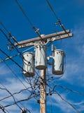 Электрический поляк с трансформаторами и проводами Стоковая Фотография