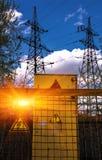 электричество Знак опасно высоковольтный и линия высокого напряжения Стоковые Изображения RF
