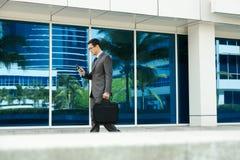 Электронная почта чтения бизнесмена на мобильном телефоне идя к офису Стоковое Изображение RF