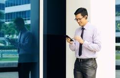 Электронная почта чтения бизнесмена на мобильном телефоне идя к офису Стоковое фото RF