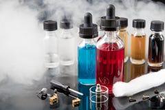 Электронные жидкости сигареты с дымом на черной предпосылке Стоковые Изображения