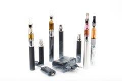 Электронные сигареты с заряжателем и дымом на белой предпосылке Стоковое Изображение
