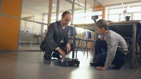 Электронный, водопод, автомобиль литьего-ионного аккумулятора Учитель показывая студенту школы дружественный к эко будущий автомо сток-видео