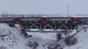 Электропоезд в движении на мосте в зиме акции видеоматериалы
