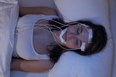 Электроэнцелфалограммы женщины уснувшие measering например в лаборатории сна Стоковые Изображения