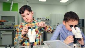 Элементарные мальчики времени делая науку экспериментируют в лаборатории школы акции видеоматериалы