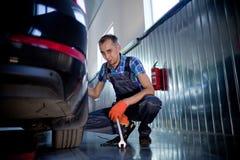 Элемент автоматического механика работая под поднятым автомобилем Стоковая Фотография