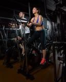 Эллиптические человек и женщина тренера ходока на черном спортзале Стоковое Изображение