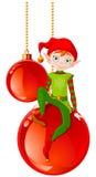 Эльф рождества сидя на шарике Стоковое Изображение RF