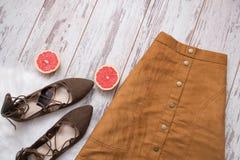 Юбка замши Брайна, коричневые ботинки замши, отрезанные половины грейпфрута Деревянная предпосылка женщина состава способа сторон Стоковые Фото