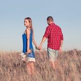 любовная история девушки сада мальчика целуя Красивые молодые пары идя в луг, внешний Стоковые Фотографии RF