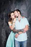 любовная история девушки сада мальчика целуя Молодые пары в голубом платье и tshort в студии Стоковые Фото