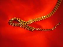 Ювелирные изделия золота на красном подарке дня валентинок заднего падения сатинировки Стоковое фото RF