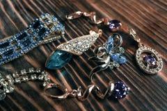 Ювелирные изделия золота с диамантами на деревянной предпосылке Стоковые Фотографии RF