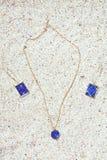 Ювелирные изделия установили в акватические тени и геометрические формы на песке приставают предпосылку к берегу стоковые фото