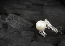 Ювелирные изделия с гениальным и pearl на черной предпосылке угля, нежности Стоковое фото RF