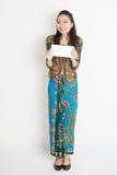 Юговосточная азиатская рука девушки держа карточку белой бумаги Стоковое фото RF
