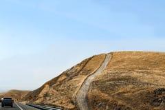 Юговосточное шоссе Калифорнии при дорога идя почти прямо вверх по холму покрытому с коричневой травой которую очевидно горела стоковые изображения rf