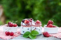 Югурт с вишней и клубниками, квадратом Разбрасывают ягоды голубик и клубник на таблицу Стоковое Изображение