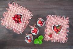 Югурт с вишней и клубниками, квадратом Разбрасывают ягоды голубик и клубник на таблицу Стоковая Фотография RF