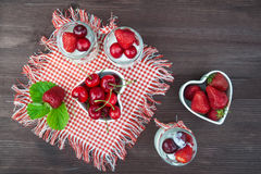 Югурт с вишней и клубниками, квадратом Разбрасывают ягоды голубик и клубник на таблицу Стоковые Фото